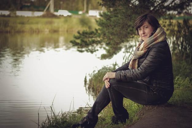 Ładny turysta dziewczyna siedzi na dużym kamieniu nad jeziorem.