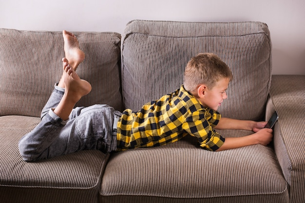 Ładny uśmiechający się chłopiec rozmawia z rodziną i przyjaciółmi, nawiązując połączenie wideo przez telefon, siedząc na kanapie. zostań w domu, zamknij się, zdystansuj się, poddaj kwarantannie.