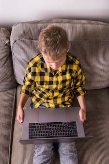 Ładny uśmiechający się chłopiec rozmawia z rodziną i przyjaciółmi, nawiązując wideorozmowę na laptopie, siedząc na kanapie. zostań w domu, zamknij się, zdystansuj się, poddaj kwarantannie.