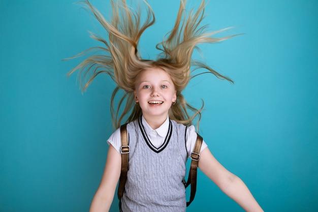 Ładny uśmiechający się dziewczyna w szkolnej sukience z plecakiem na białym tle.