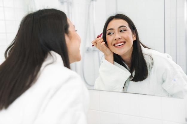 Ładny uśmiechający się szczęśliwa młoda kobieta w domu w łazience, poprawiając brwi.