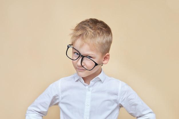 Ładny, uśmiechnięty chytry chłopak w krzywe okulary patrzy na kamery