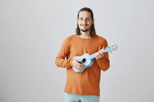 Ładny uśmiechnięty mężczyzna gra na ukulele