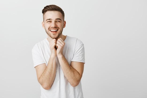 Ładny uśmiechnięty młody człowiek w białej koszulce robi uroczej twarzy