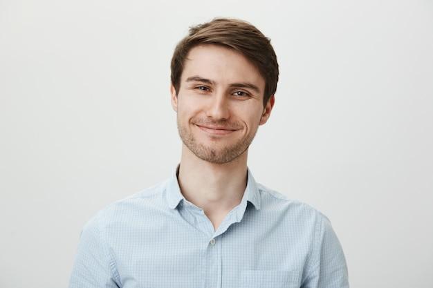 Ładny uśmiechnięty młody człowiek z włosia szuka zadowolonego