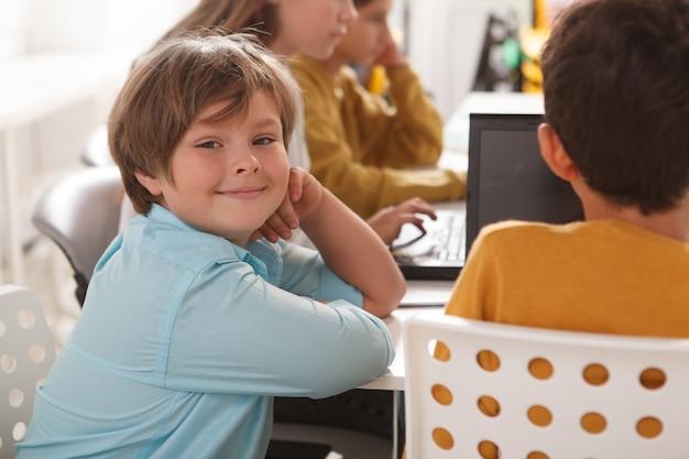 Ładny wesoły chłopiec uśmiecha się do kamery podczas nauki z kolegami z klasy w szkole komputerowej