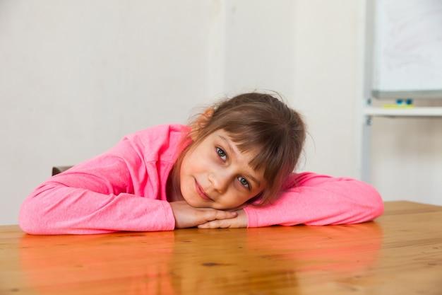 Ładny wesoły portret dziewczynki na stole