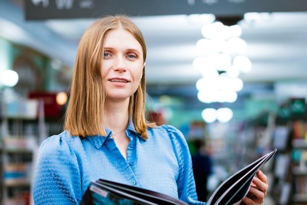 Ładny widok kobiety trzymającej otwartą papierową książkę czytającą bestseller z księgarni lub księgarni