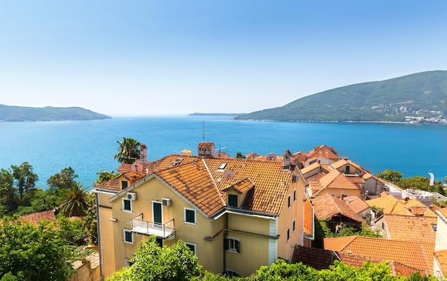 Ładny widok na błękitne duże morze z ceglanymi budynkami?