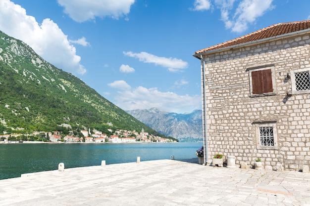 Ładny widok na niebieskie duże jezioro z ceglanym budynkiem?
