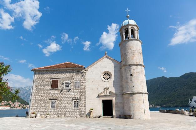 Ładny widok na niebieskie duże jezioro z ceglanym kościołem?