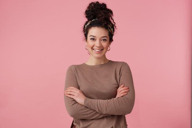 Ładny wygląd kobiety, piękna dziewczyna z ciemnymi kręconymi włosami kok. nosi opaskę, kolczyki i brązowy sweter. uzupełniał. trzyma ręce skrzyżowane