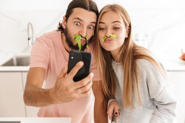 Ładny zabawny młody kochający para w kuchni w pomieszczeniu w domu gotowanie razem wziąć selfie przez telefon komórkowy zabawy.