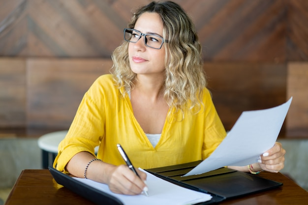 Ładny żeński dyrektor wykonawczy pracuje z dokumentami przy stołem