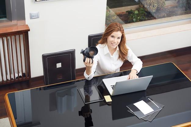 Ładny żeński fotograf pracuje w domu