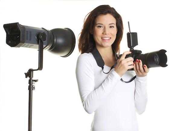 Ładny żeński fotograf pracuje w studiu