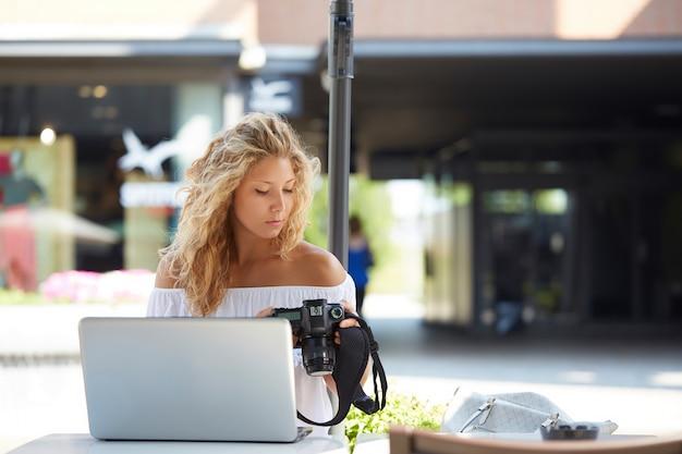 Ładny żeński fotograf pracuje z laptopem przy kawiarnią