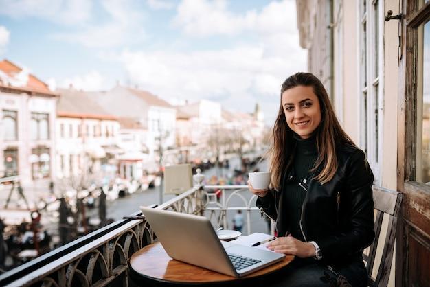 Ładny żeński jounalist pracuje na zewnątrz w kawiarni. patrząc na aparat.