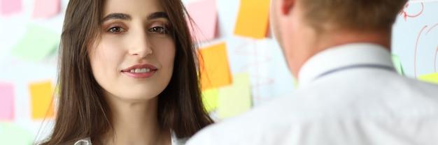 Ładny żeński pracownik biurowy konsultuje jej męskiego współpracownika