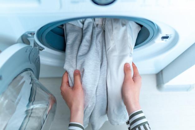 Ładowanie białych ubrań i bielizny do pralki. robi pranie w domu. widok z góry