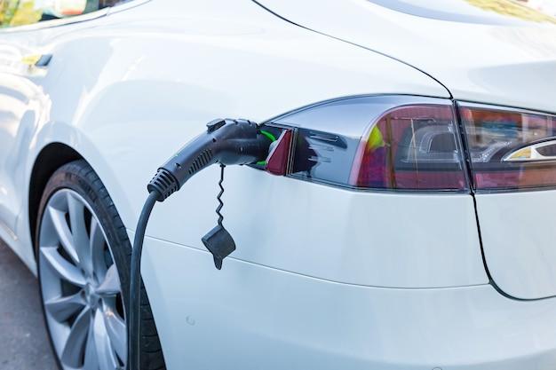 Ładowanie energii elektrycznej pojazdu elektrycznego. elektryczna stacja ładowania samochodów z autem ev