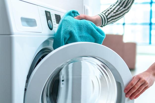 Ładowanie ręcznika, odzieży i pościeli do pralki. robi pranie w domu. obowiązki domowe i sprzątanie