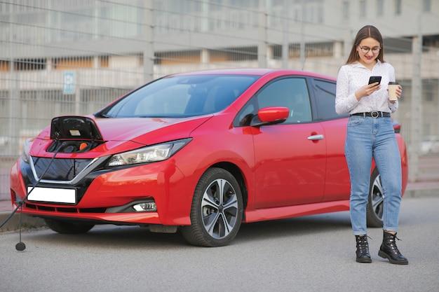 Ładowanie samochodu elektrycznego na ulicy. ekologiczne akumulatory samochodowe podłączone i ładujące. dziewczyna korzysta z napoju kawowego podczas korzystania ze smartfona i oczekiwania na zasilacz podłącz do pojazdów elektrycznych w celu naładowania