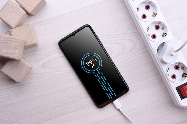 Ładowanie smartfona do telefonu komórkowego na drewnianym stole z przedłużaczem