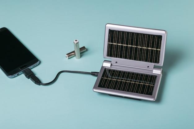 Ładowanie smartfona ze źródła energii elektrycznej zasilanej słońcem. wykorzystanie energii słonecznej. technologia przyszłości.