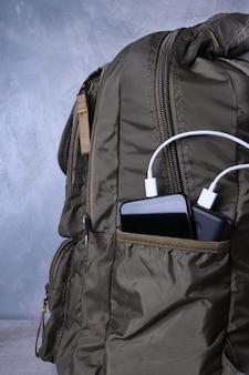Ładowanie telefonu, powerbank ładuje smartfon, telefon komórkowy z bankiem energii. głębia ostrości na power banku w torbie plecaka
