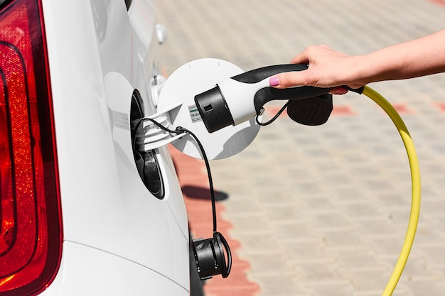Ładowanie zasilacza samochodu elektrycznego na ładowarce. zbliżenie dłoni kobiety wkładając wtyczkę ładowarki do pojazdu elektrycznego.