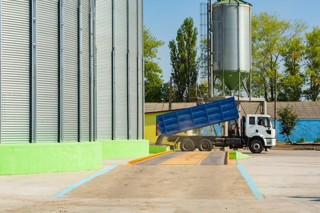 Ładowanie zboża ciężarówkami na windę do metalowych pojemników.