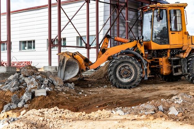 Ładowarka czołowa na placu budowy usuwa gruz ze zbrojonego betonu. zbieranie i usuwanie oderwanych materiałów budowlanych.