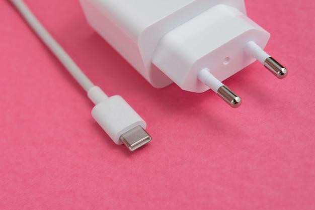 Ładowarka i kabel usb typu c na różowym tle