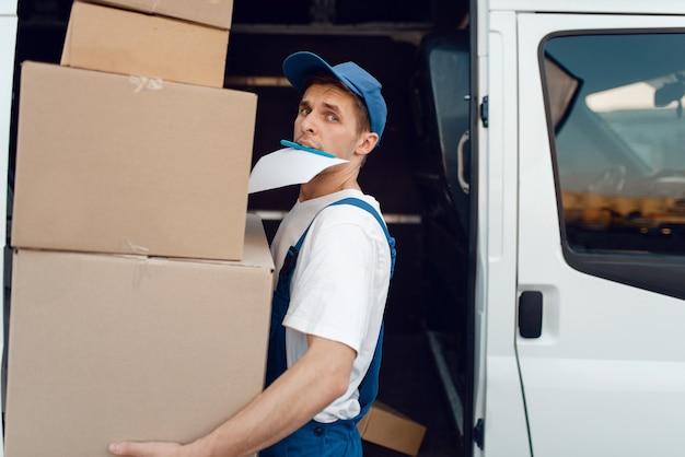 Ładowarka w jednolitym stosie paczek, usługa dostawy. mężczyzna stojący przy kartonowych paczkach w pojeździe, mężczyzna dostawy, kurier lub wysyłka