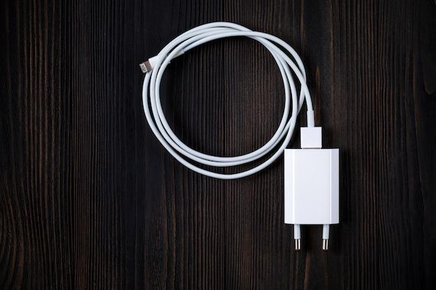 Ładowarki do telefonów kablowych na tle drewna