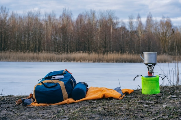 Ładuj smartfon podczas podróży z powerbankiem. przenośna ładowarka ładuje telefon na tle turystycznego palnika gazowego i lasu.
