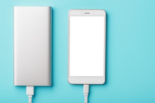Ładuje telefon z powerbank na błękitnym tle. trzymaj baterię naładowaną w urządzeniu, gdziekolwiek jesteś.