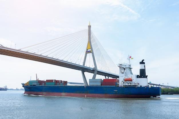 Ładunek statku przewożącego kontener i działającego pod mostem dla towarów eksportowych.
