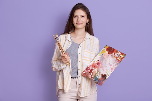 Lady artist stojąca przed liliową ścianą studia, urocza młoda kobieta trzyma nowy obraz i maluje pędzel w dłoniach