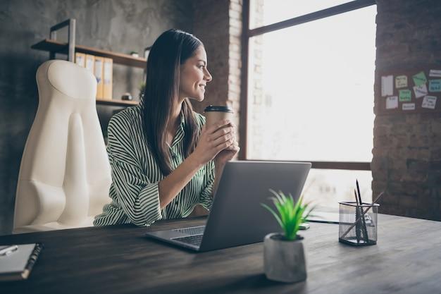Lady freelancer siedzi przy stole i pije herbatę na wynos w biurze