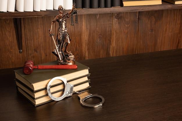 Lady justice, młotek sędziego, książki, kajdanki na starym drewnianym stole