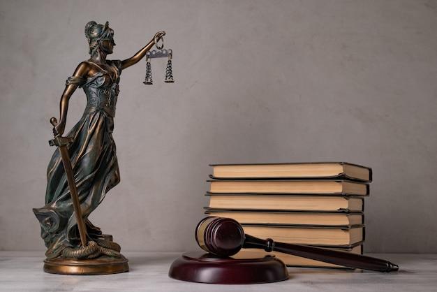 Lady justice, młotek sędziego, książki na starym drewnianym stole