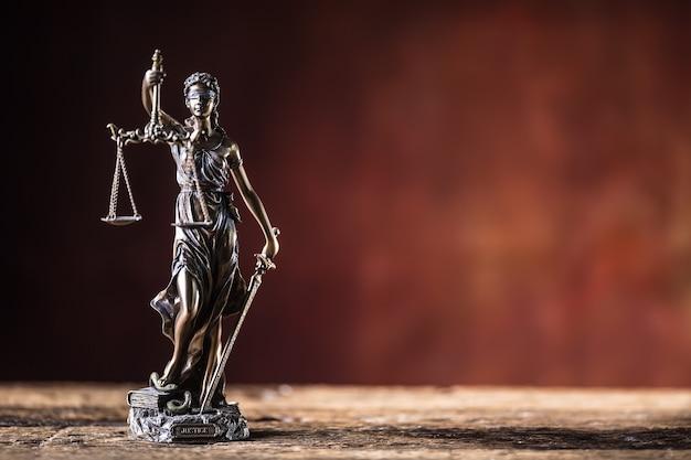 Lady justicia trzyma miecz i łuskę brązową figurkę na drewnianym stole.