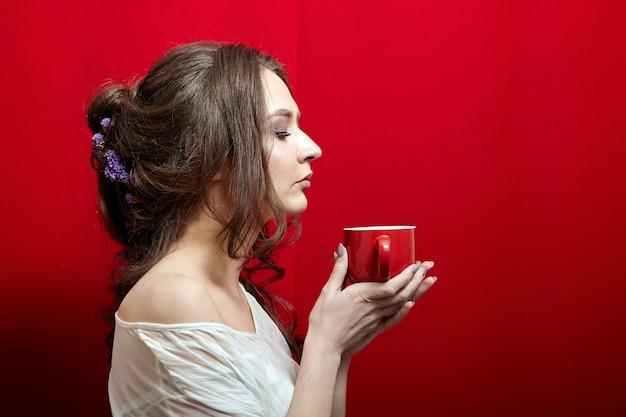 Lady zaciąga się aromatem kawy lub herbaty. młoda kobieta z filiżanką napoju w dłoniach