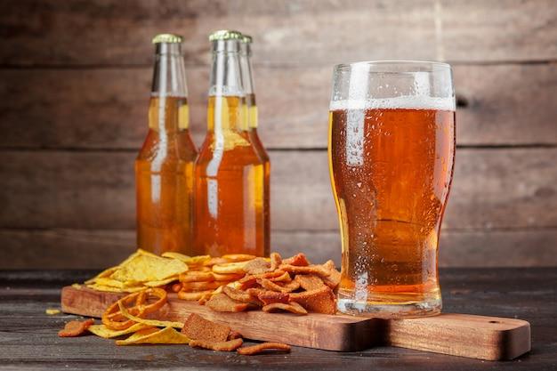 Lager piwo i przekąski na drewnianym stole. orzechy, frytki, precel