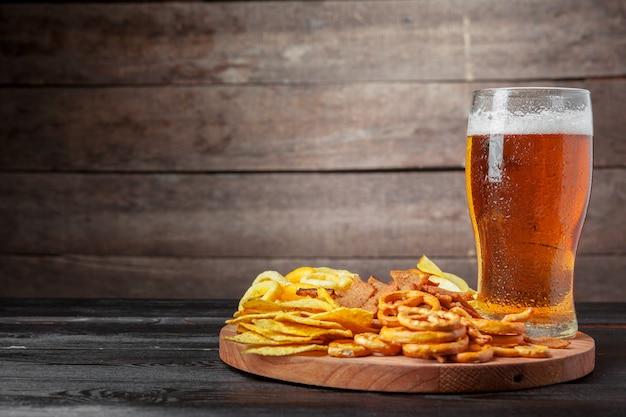 Lager piwo i przekąski na drewnianym stole.