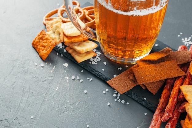 Lager piwo i przekąski na kamiennym stole. krakers, widok z boku żetonów