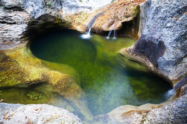 Laguna w zielonej, spokojnej wodzie otoczona letnimi wodospadami i skałami