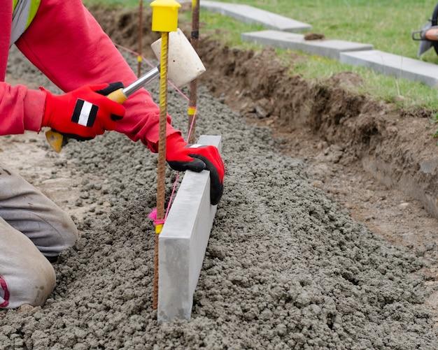Laing krawężnika na półsuchym betonie podczas robót drogowych i budowy nowej chodnika przez robotnika ziemnego w rękawicach ochronnych